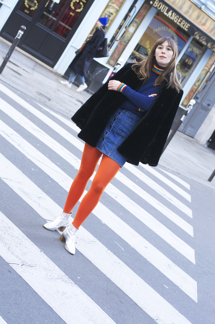 Being bold and wearing orange tights, a mini skirt and rainbow knit in Paris