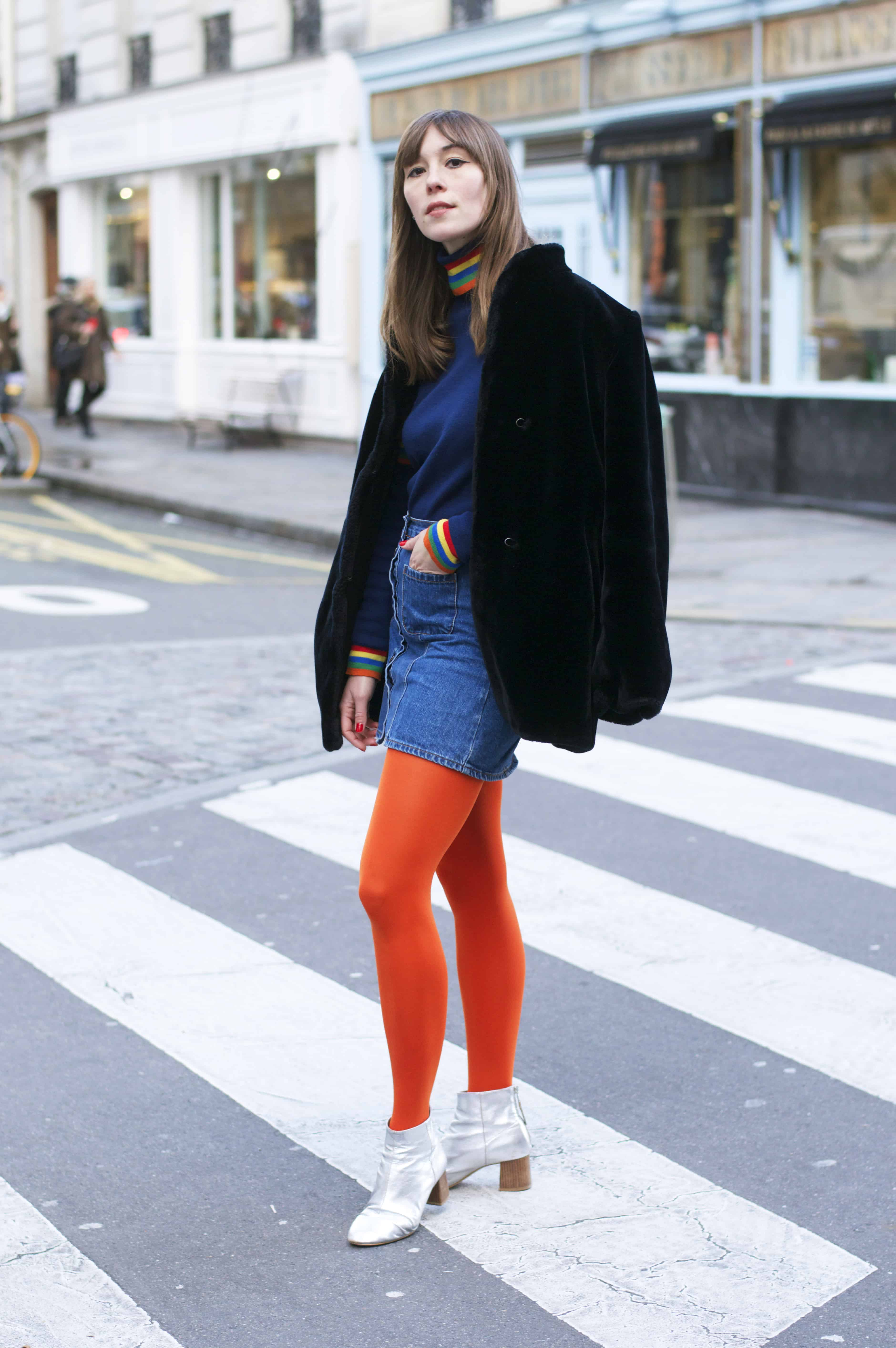Wearing bold orange tights and black faux fur coat in Paris