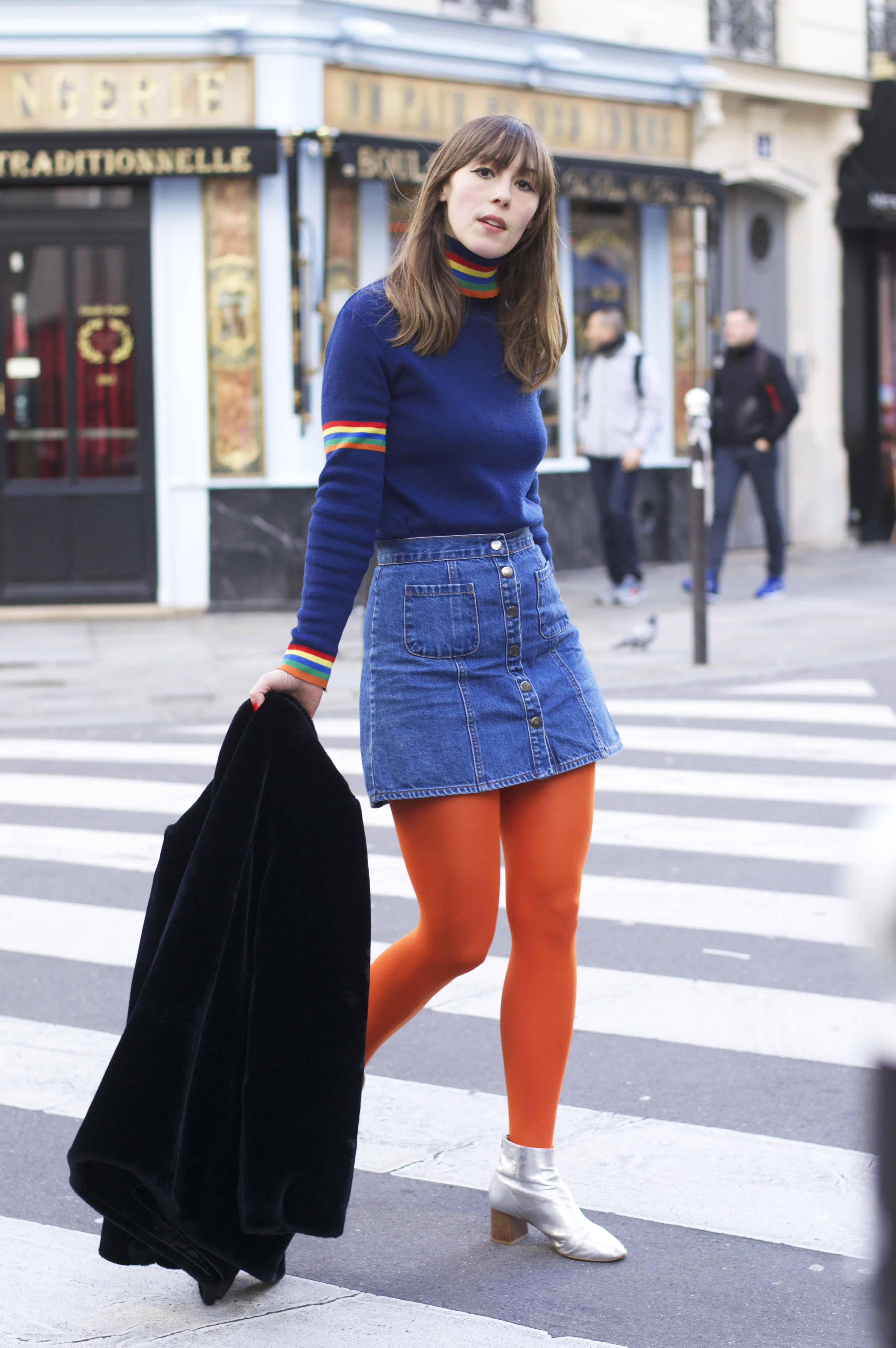 Wearing bold orange tights and a rainbow knit in Paris