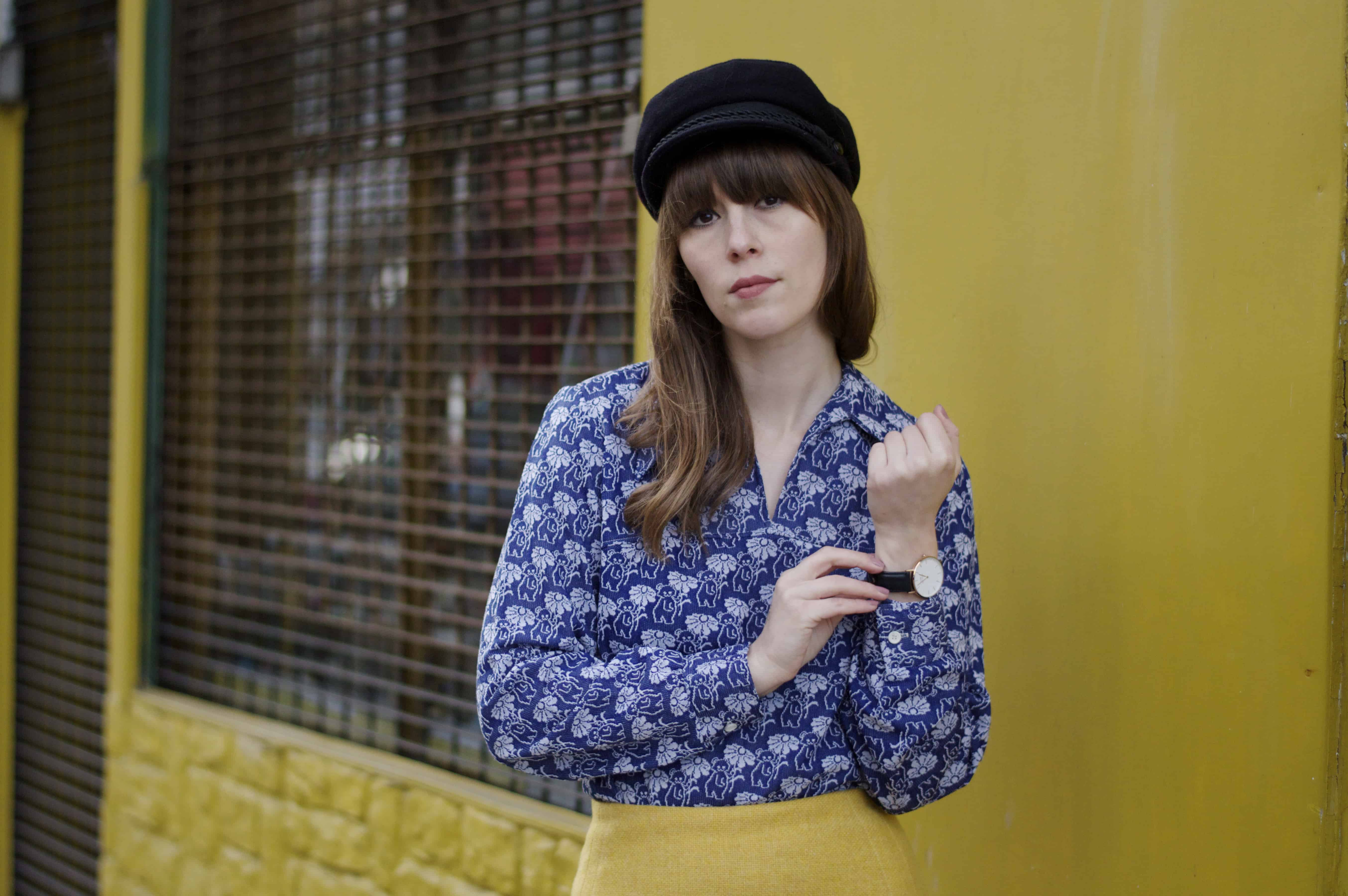Wearing a blue printed seventies shirt against a yellow wall